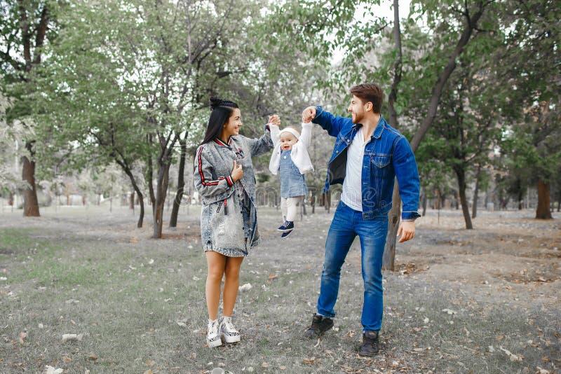 Familjen går i parkerar, modern håller den lilla dottern ovanför hennes huvud, fadern tar omsorg av familjen arkivbild