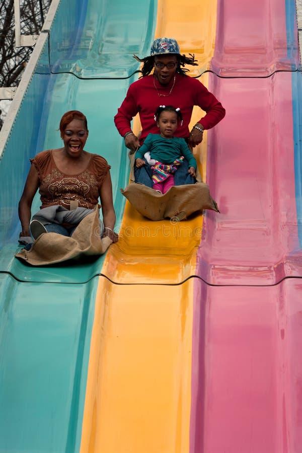 Familjen går ner rolig glidbana på den Atlanta mässan royaltyfria foton