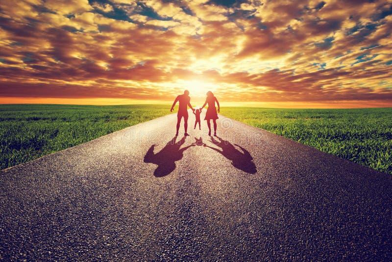 Familjen går på den långa raka vägen, väg in mot solnedgångsolen royaltyfri bild