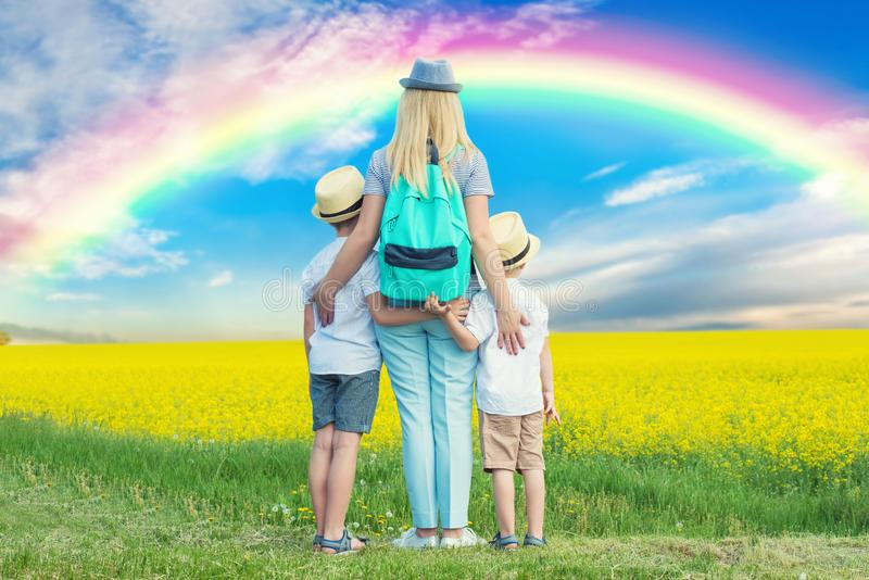 Familjen går till och med det blomma fältet och blicken på regnbågen i himlen royaltyfri foto