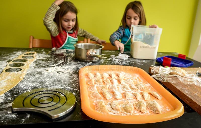 Familjen gör den hem gjord bakelseklimptortellinien eller raviol fotografering för bildbyråer