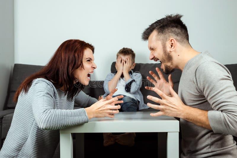 Familjen grälar, pomaen, och farsan svär i bakgrunden av sonen, som inte gillar den, barnskriken Begreppet av familjen fotografering för bildbyråer