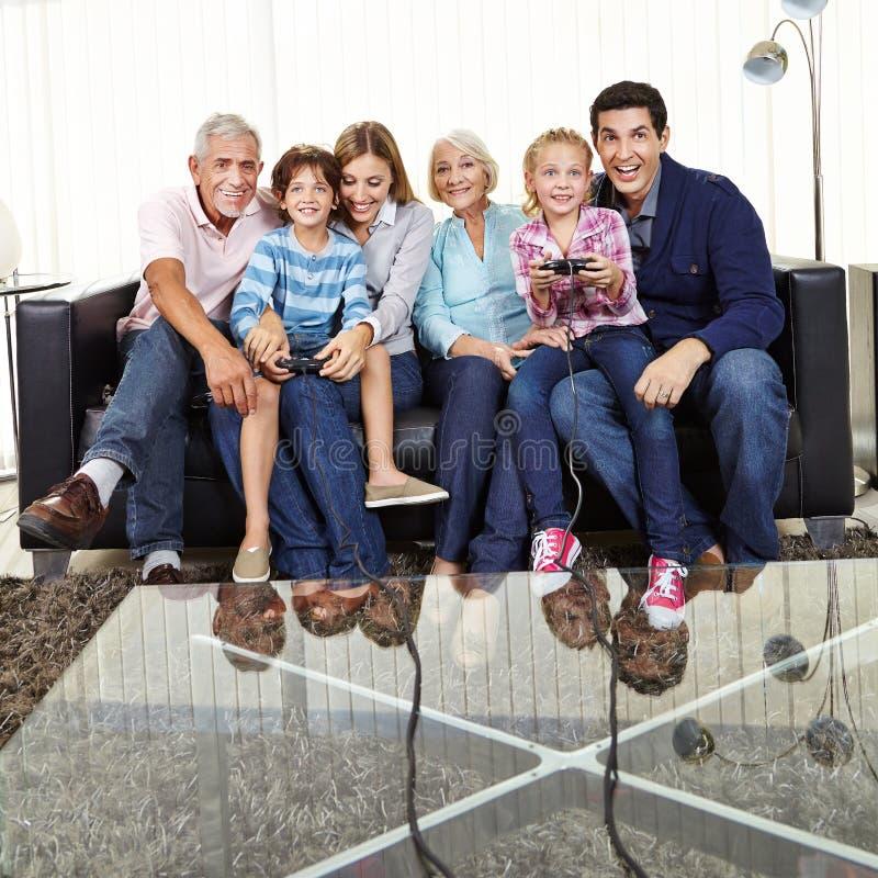 Familjen håller ögonen på barn att spela videospel royaltyfri bild