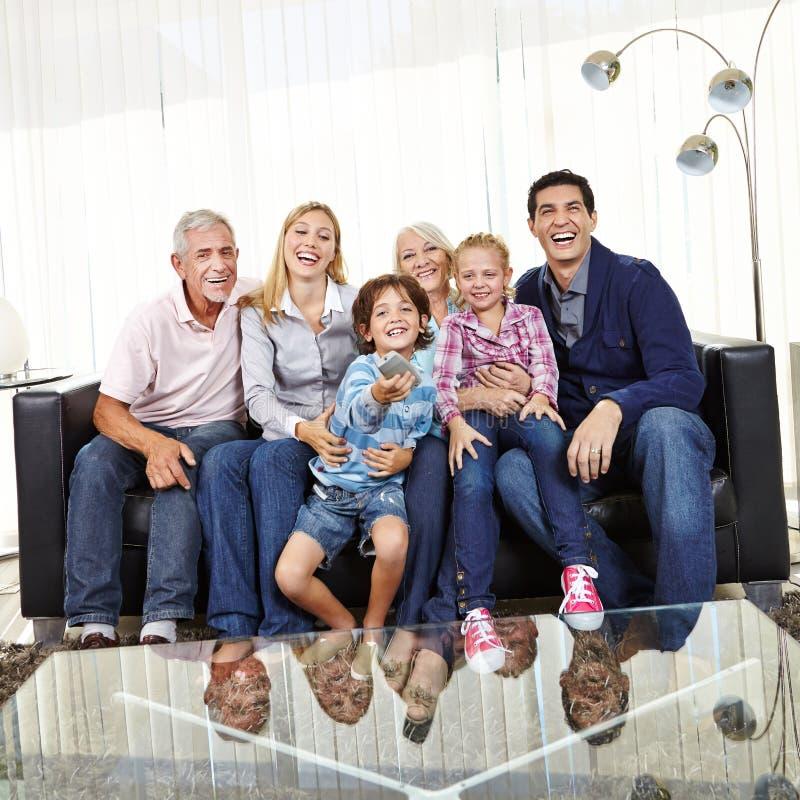 Familjen håller ögonen på TV tillsammans royaltyfria foton