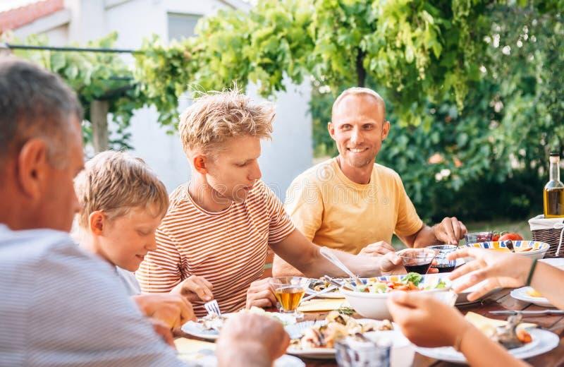 Familjen har en matställe på öppen luft i sommarträdgård royaltyfri bild