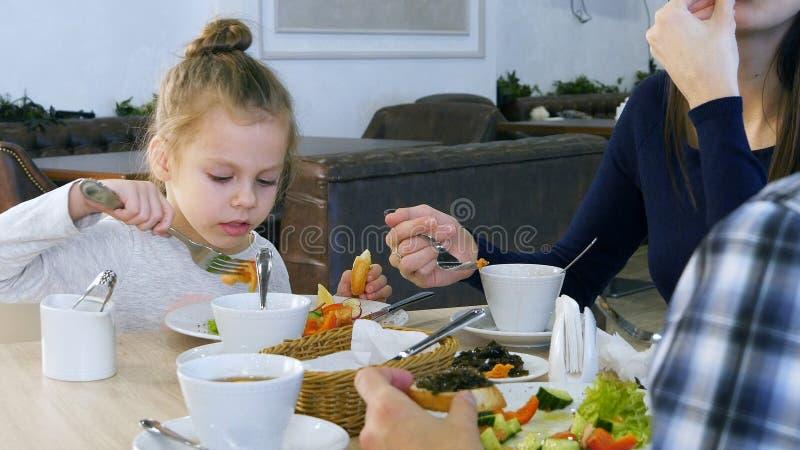 Familjen har sund lunch på restaurangen Liten dotter som äter grönsaksallad med vitt bröd arkivbild