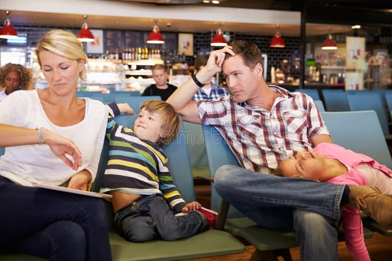 Familjen i flygplatsavvikelsevardagsrum väntar på försenat flyg royaltyfri foto