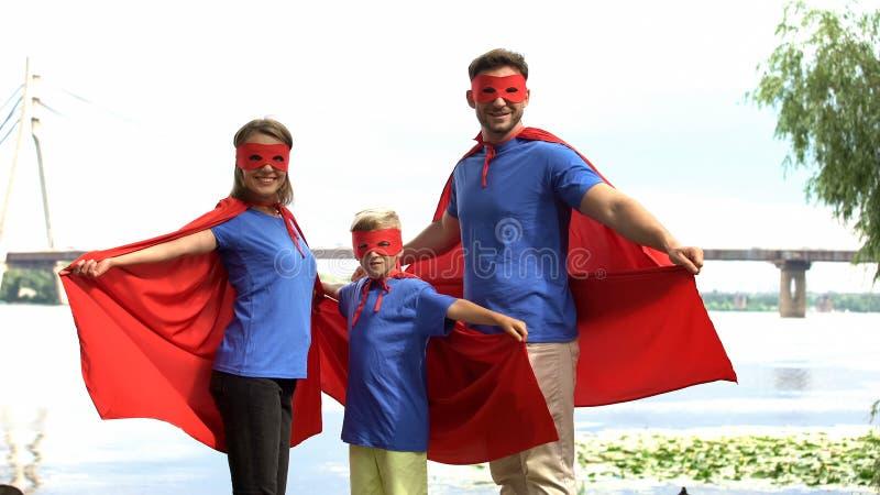 Familjen i superhero kostymerar att posera för kamera, samhörighetskänsla, och utomhus- vila royaltyfri fotografi