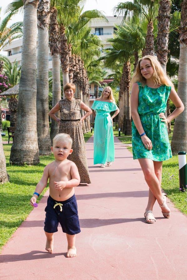 Familjen inkluderar farmodern, modern, flickan och pojken i parkera arkivfoton