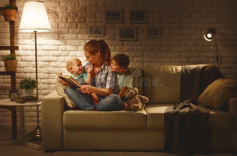 Familjen, innan den går att bädda ned modern, läser barnboken om lampan royaltyfri fotografi