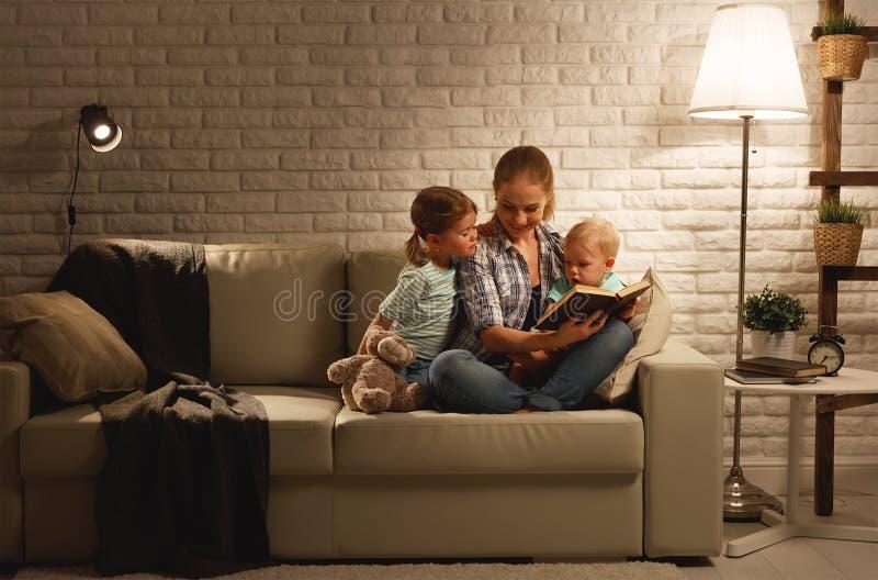 Familjen, innan den går att bädda ned modern, läser barnboken om lampan royaltyfri bild