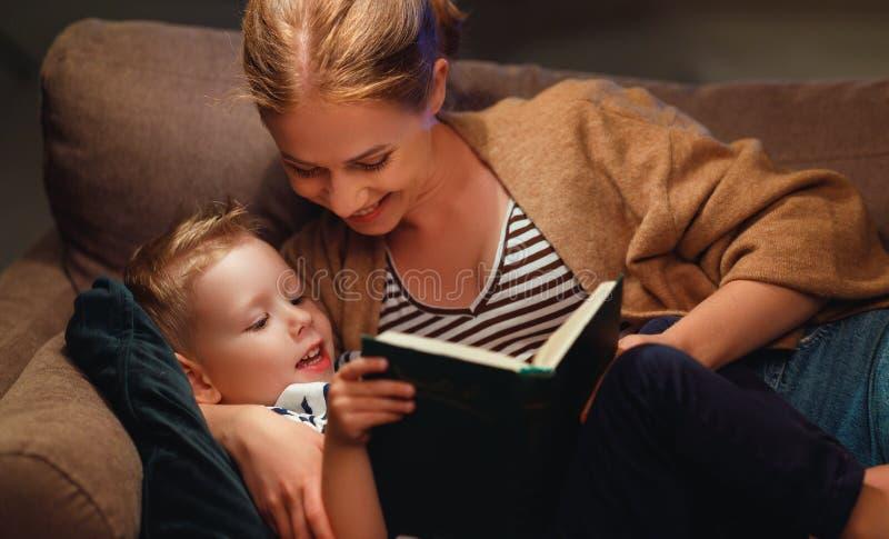 Familjen, innan den går att bädda ned modern, läser till hennes barnsonbok nära en lampa arkivbilder