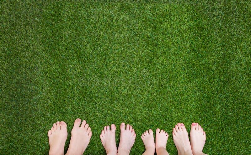 Familjen lägger benen på ryggen anseende tillsammans på grönt gräs arkivbild