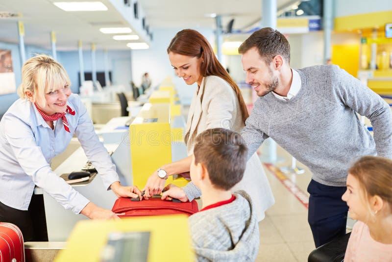 Familjen med barn på flygplatsen kontrollerar in räknaren royaltyfri foto