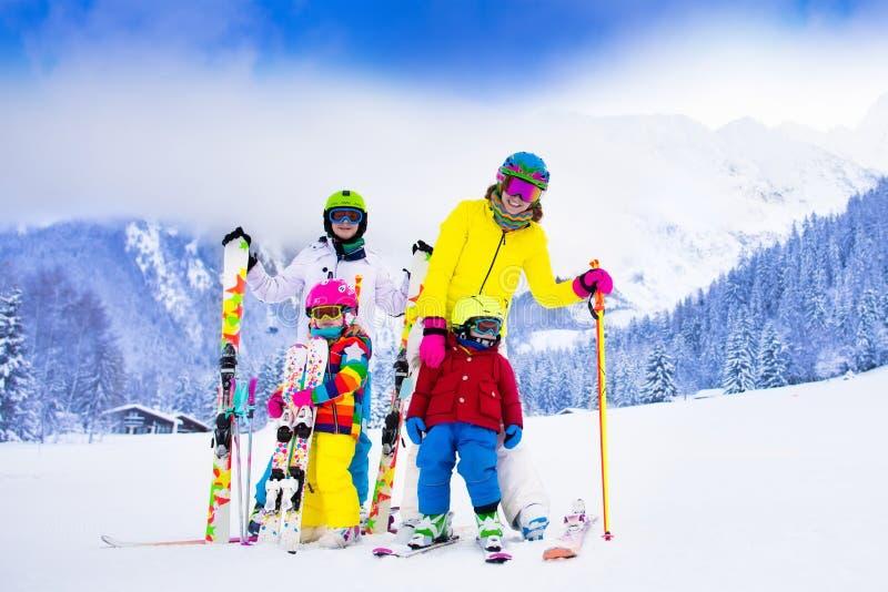 Familjen med barn på vinter skidar semestern royaltyfri bild