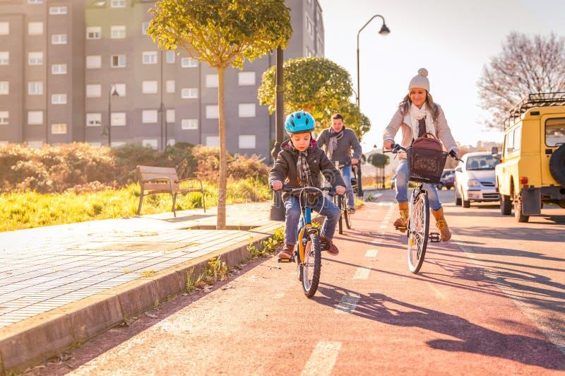Familjen med barnridning cyklar i staden arkivbild