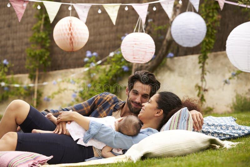 Familjen med behandla som ett barn att koppla av på filten i trädgård tillsammans royaltyfria bilder