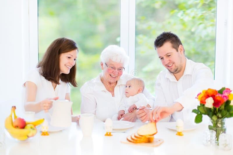 Familjen med behandla som ett barn ha frukosten med drandmother arkivbild