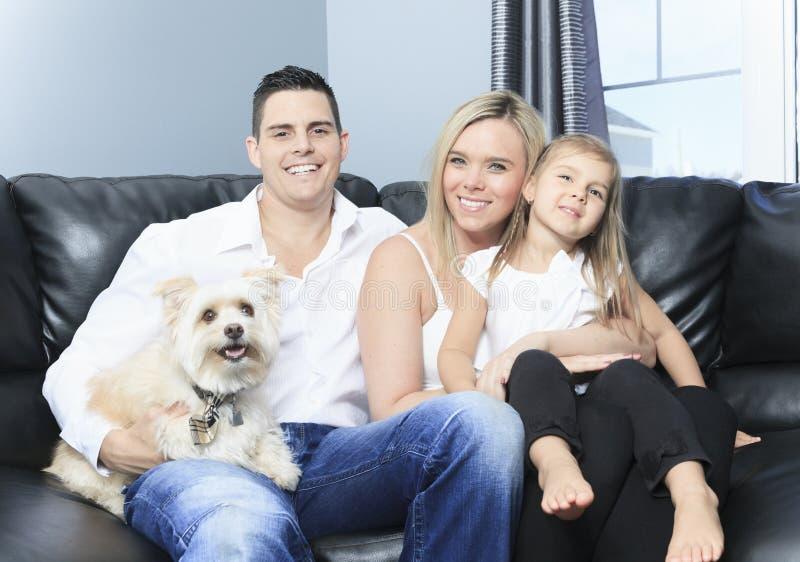 Familjen med husdjur sitter på soffan hemma royaltyfri fotografi