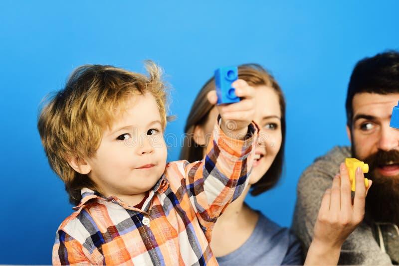 Familjen med nyfikna framsidor spenderar tid i lekrum fotografering för bildbyråer