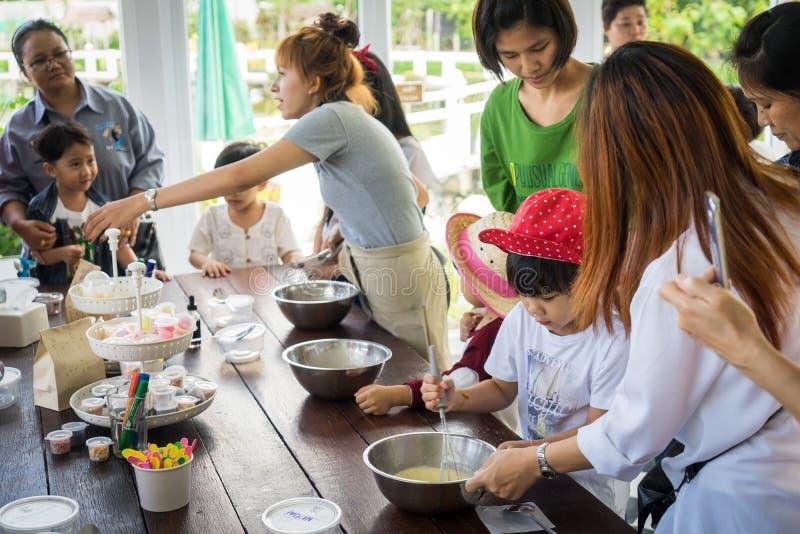 Familjen med småbarn lagar mat i en bagerimatlagninggrupp arkivfoto