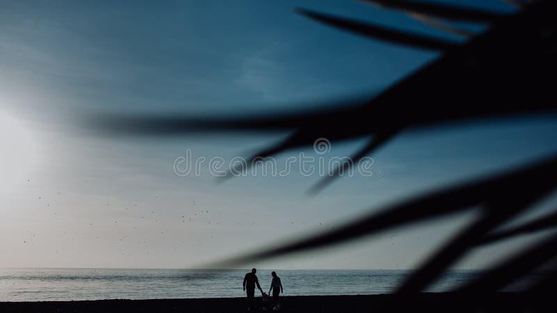 Familjen med st?llningar f?r ett barn mot solnedg?nghavsstranden och g?mma i handflatan Tropiskt semesterbegrepp silhouette royaltyfri fotografi