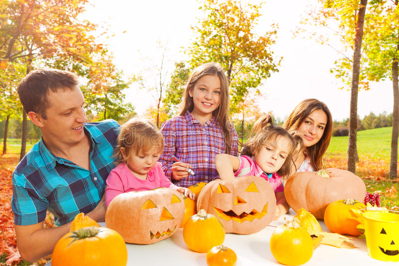 Familjen med ungar förbereder pumpor för allhelgonaafton royaltyfri fotografi