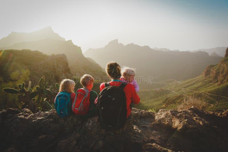 Familjen med ungar reser att fotvandra i berg som ser sikt royaltyfria bilder