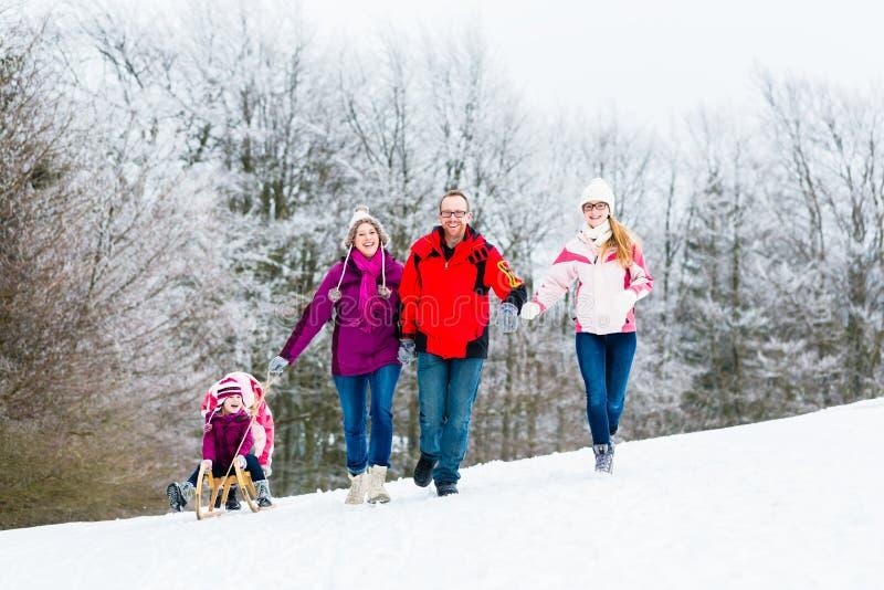 Familjen med ungar som har vinter, går i snö royaltyfri fotografi