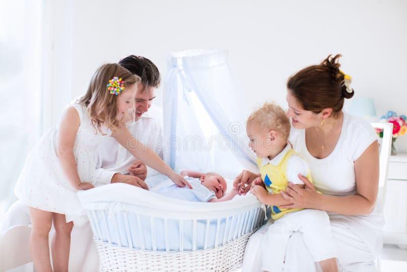 Familjen med ungar som spelar med nyfött, behandla som ett barn fotografering för bildbyråer
