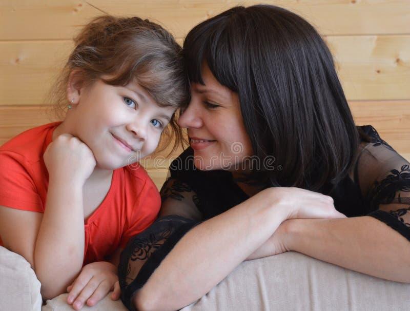 Familjen modern, barnet som är lyckligt, behandla som ett barn, kvinnan, förälskelse, dottern som är ung, säng, mamman, folket, p arkivbilder