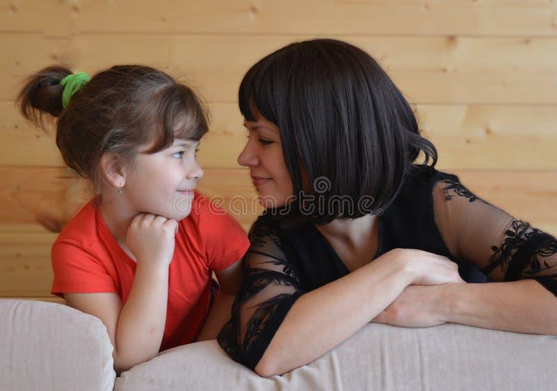 Familjen modern, barnet som är lyckligt, behandla som ett barn, kvinnan, förälskelse, dottern som är ung, säng, mamman, folket, p arkivfoton