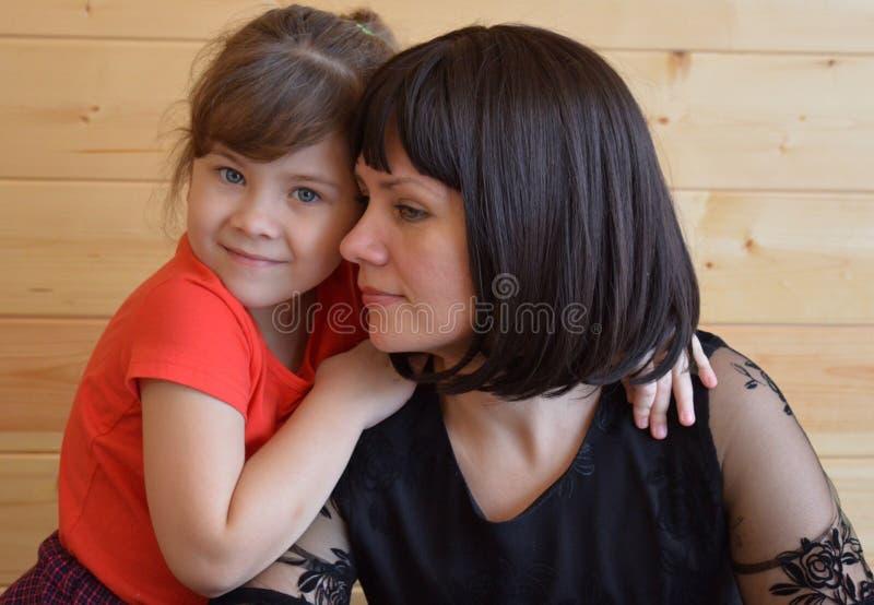 Familjen modern, barnet som är lyckligt, behandla som ett barn, kvinnan, förälskelse, dottern som är ung, säng, mamman, folket, p royaltyfri foto