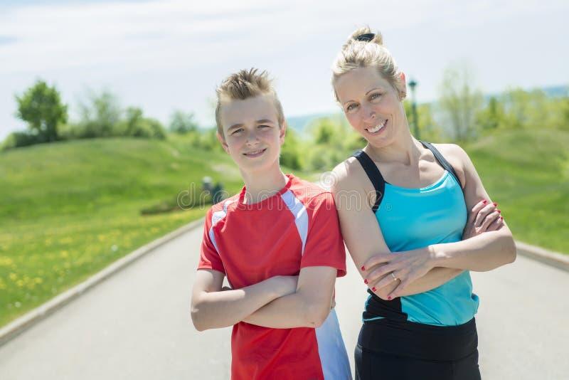 Familjen, modern och sonen är köra eller jogga för sport utomhus royaltyfria bilder