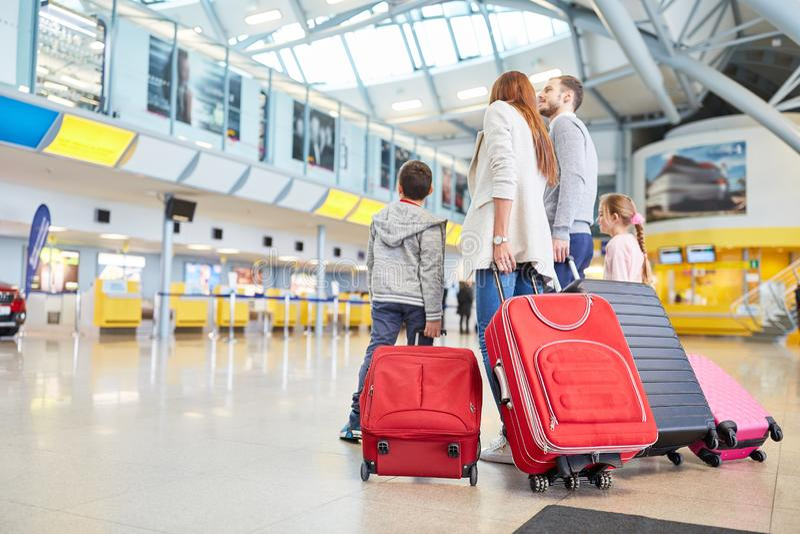 Familjen och barn i flygplatsen väntar på avvikelse arkivfoto