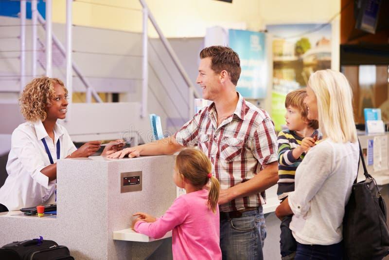 Familjen på flygplatsen kontrollerar in skrivbordet som lämnar på semester royaltyfri bild