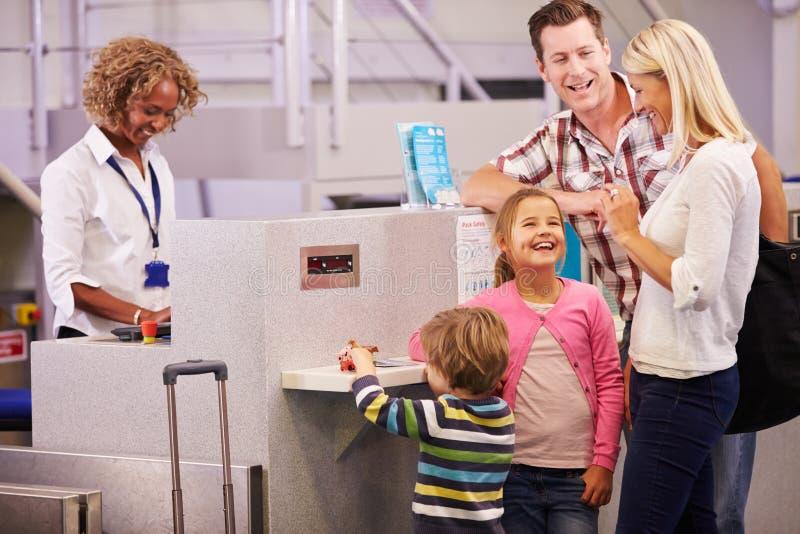 Familjen på flygplatsen kontrollerar in skrivbordet som lämnar på semester arkivbild
