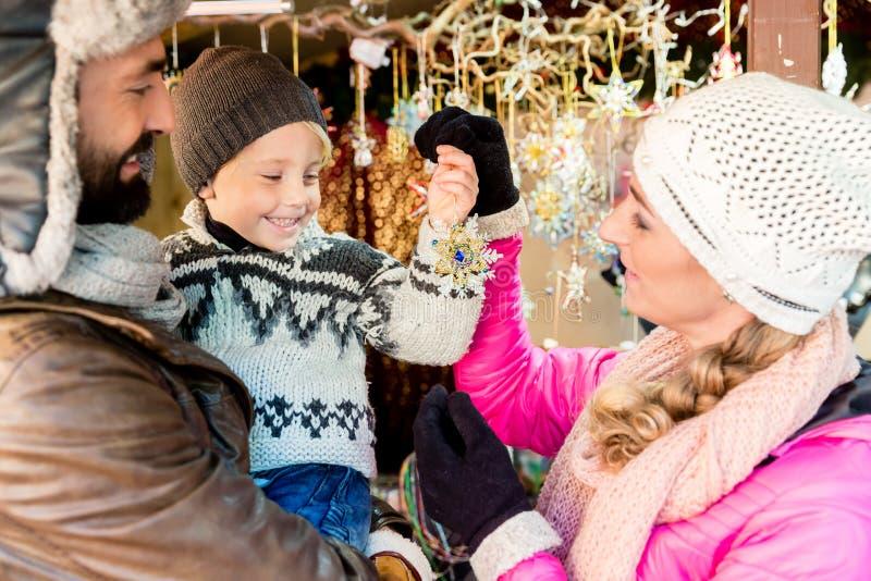 Familjen på jul marknadsför köpande prydnader och struntsaker arkivbilder