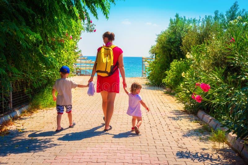 Familjen på sommar vilar modern, och barn går till havsstranden fotografering för bildbyråer