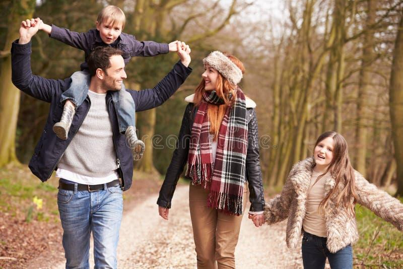 Familjen på vinterbygd går tillsammans royaltyfri fotografi