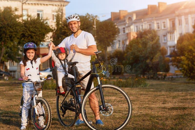 Familjen parkerar in ridningcyklar Ritt för två flickor som cyklas med deras fader arkivfoto