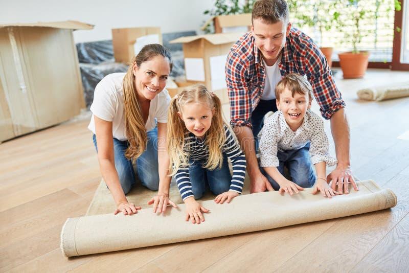 Familjen rullar ut matta, när den flyttar sig fotografering för bildbyråer