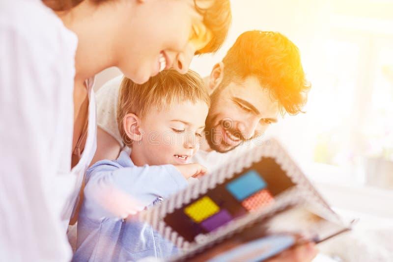 Familjen ser den fotoalbumet eller bilderboken med sonen royaltyfria foton