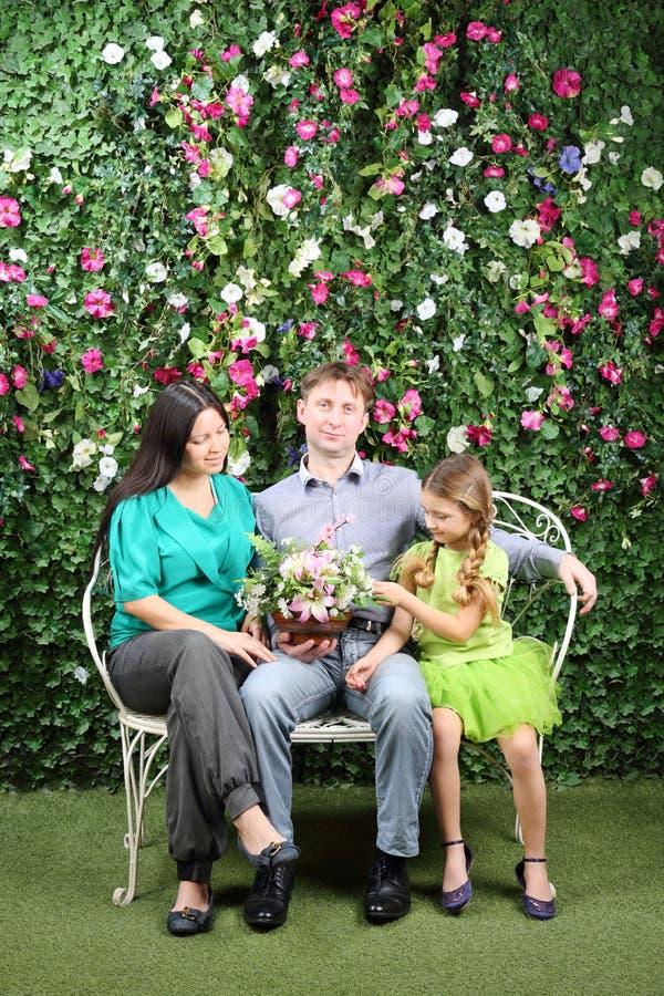 Familjen sitter på den vita bänken med gruppen av blommor arkivbilder