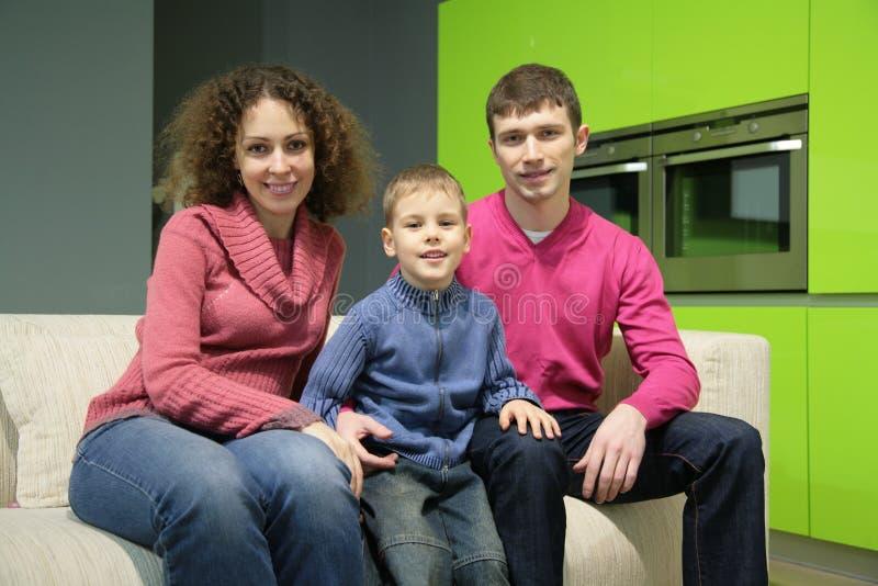 Familjen sitter på sofaen royaltyfria foton