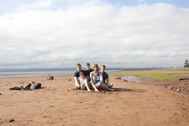 Familjen sitter på stranden royaltyfria foton