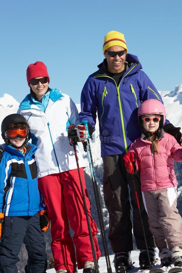 Familjen skidar på ferie i berg arkivbild