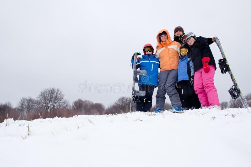 Familjen skidar på ferie i berg arkivfoto