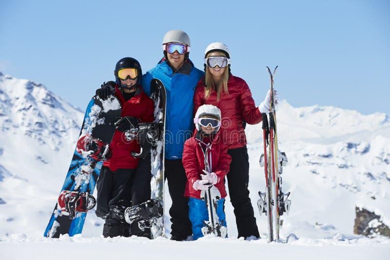 Familjen skidar på ferie i berg royaltyfri bild