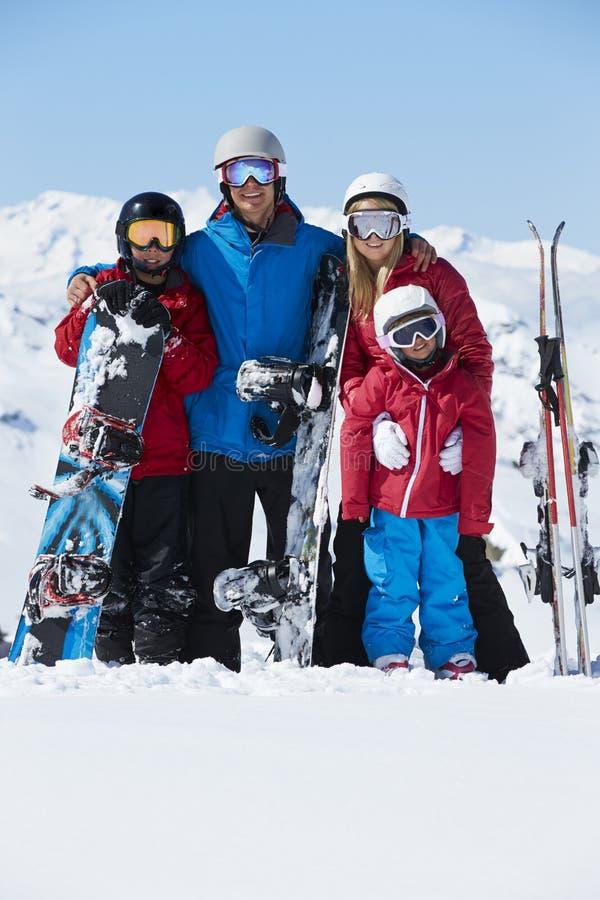 Familjen skidar på ferie i berg royaltyfri foto